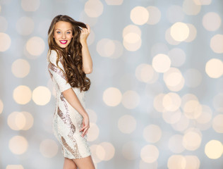 happy young woman or teen in dress over lights