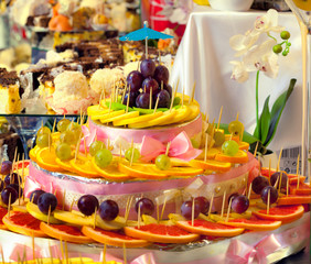 Sliced fruits and sweets for wedding table