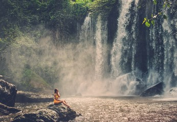 Beautiful woman sitting near waterfall enjoying the sun, Phnom Koulen at Siem Reap, Cambodia Wall mural