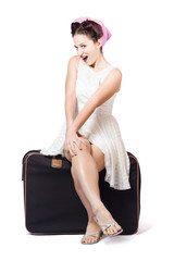 Female pinup travelling tourist sitting on luggage