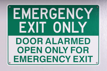Emergency exit wall sign in green on off white background on a wall, Australia 2015  Wall mural