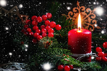 Christmas or New Year's dark composition with burning red candle