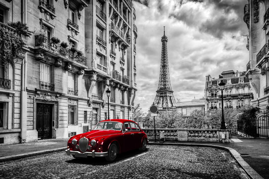 Artistic Paris, France. Eiffel Tower seen from the street with red retro limousine car.