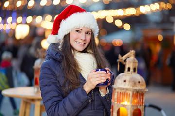 Beautiful woman with santa hat on Christmas Market