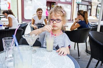 Little girl is drinking lemonade at restaurant.
