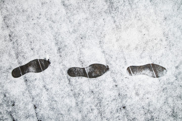 Shoe prints in the fresh snow on the wooden bridge. Danger walking in the snow on icy and frozen wooden bridge.