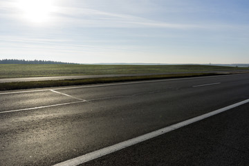 highway near the forest against sun