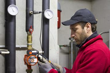 Idraulico che lavora misura la temperatura in una centrale termica