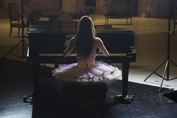 Rear view, ballerina playing piano, stage mess visible.