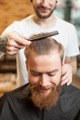 Cheerful bearded hipster is getting a cool hairstyle