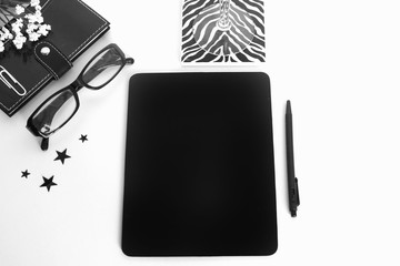 A high fashion styled white desktop with a black chalkboard for text, glasses, stars, zebra print, notebook, a stemware glass, and small white flowers.