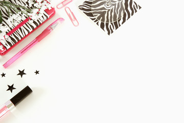 A white desktop styed photo in black, white and pink colors with paper clips, notebook, stars, stemmed glass and black and white animal print.