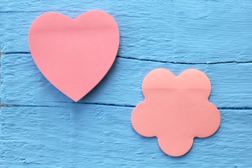 Blank pink paper note in two different shapes - flower and heart shape on grunge blue wooden background with copy space