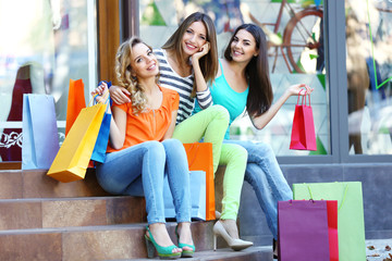 Beautiful young woman with shopping bags sitting on steps