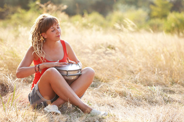 Pretty young girl inspired with a drum on the field