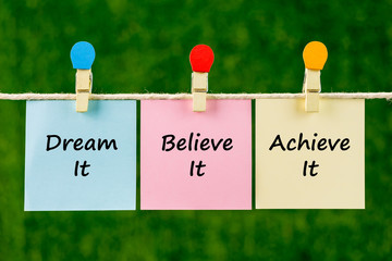Word quotes of Dream It, Believe It, Achieve It on sticky color papers hanging on rope against blurred green background.