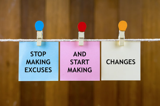 Word quotes of STOP MAKING EXCUSES AND START MAKING CHANGES on colorful sticky papers hanging by a rope against blurred wooden background.