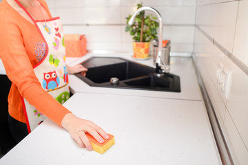 woman wiping white table with yellow sponge