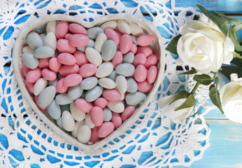 Colorful candy in white heart shaped bowl and white roses