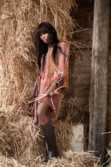 Beautiful young pretty black woman posing near the haystacks in colorful hippie dress.