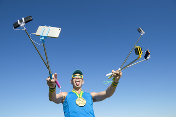 Gold medal athlete makes a face for his many gadgets on selfie sticks as he poses for a picture