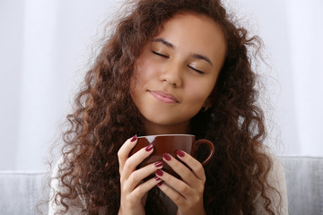 Close up portrait of pretty young woman with closed eyes drinking coffee