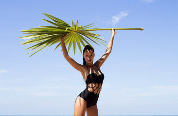 Fashion beautiful woman in bikini with palm branch on beach near sea enjoying sun. Hair up.Tropics.Hot summer day.Sexy girl.Vacation.Photo from Phuket island. Thailand