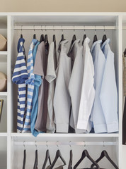 modern closet with row of shirts hanging in white wardrobe