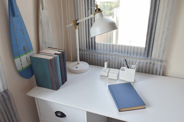 work table with lamp,pencils and books in working room