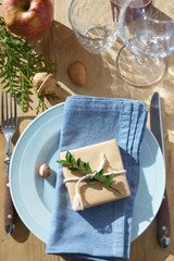 Rustic table setting: small present wrapped with kraft paper, evergreens, nuts, apple