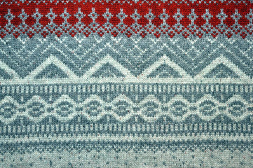 Red knitted background with Christmas patterns - sweater texture