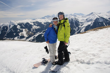 Snowboarding couple in embrace on the top of mountain