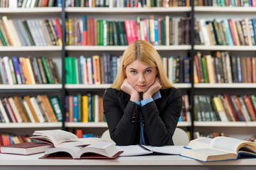 smiling young girl with blonde hair sitting at a desk in the lib