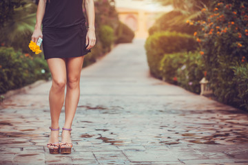 female legs in purple shoes walking in the park