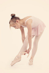 fillette attachant ses pointes danse classique