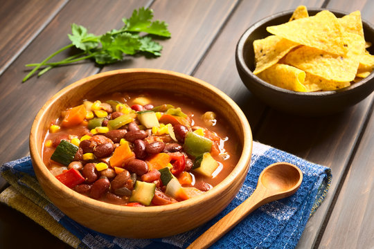 Vegetarian chili dish made of kidney bean, carrot, zucchini, bell pepper, sweet corn, tomato, onion, garlic, photographed with natural light (Selective Focus, Focus in the middle of the dish)