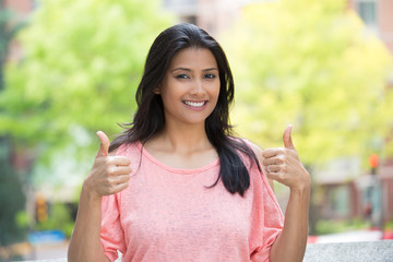 Closeup portrait of young pretty woman in pink shirt with two thumbs up sign gesture, isolated outdoors background. Positive emotion facial expression feelings, signs and symbols, body language