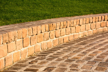 Curved sandstone brick walkway and grassy bank, bathed in afternoon sun