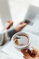 Closeup of man holding a cup of hot tea and reading newspapers