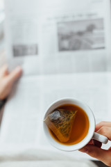 Man holding cup of tea and reading the newspapers