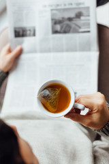 Man enjoying with a cup of tea while reading newspapers