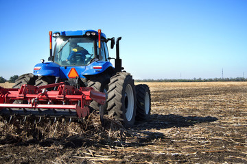 Fototapete - Farmer on a tractor plowed field