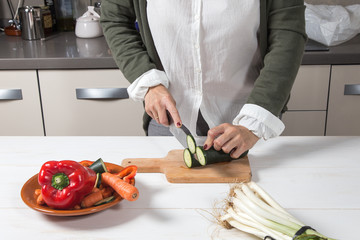Woman cutting vegetables on wooden board