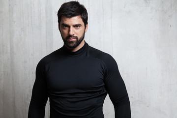 Portrait brutal athlete in sportswear on a cement background