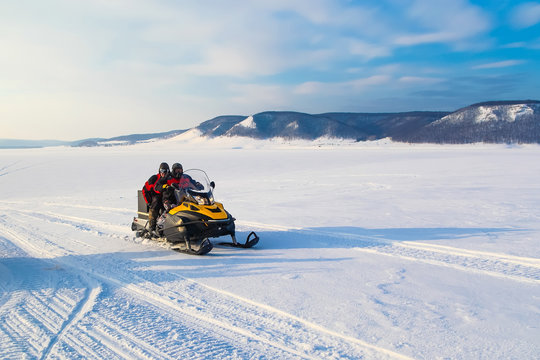 people driving  snowmobile in winter mountain