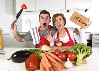 Tuinposter Koken American couple in stress at home kitchen in cooking apron asking for help frustrated