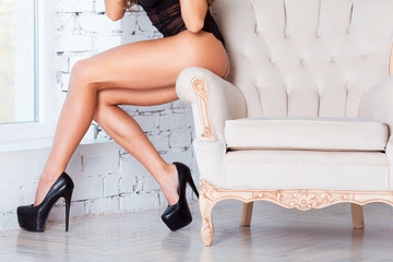 Perfect, sexy legs and ass of young woman wearing seductive black lingerie