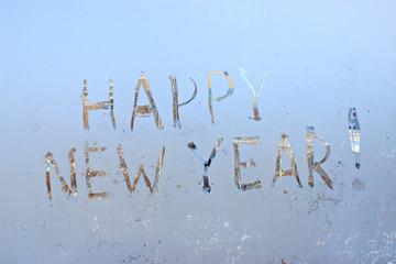 happy new year written on frosty winter window background