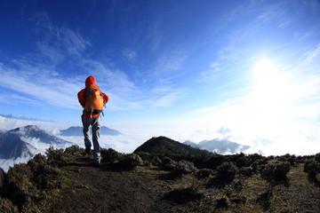 young woman backpacker hiking to beautiful mountain peak