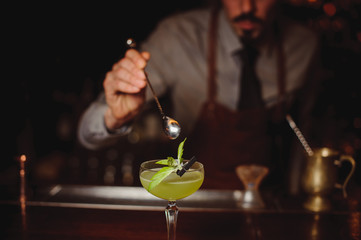 Close-up of bartender making green cocktail